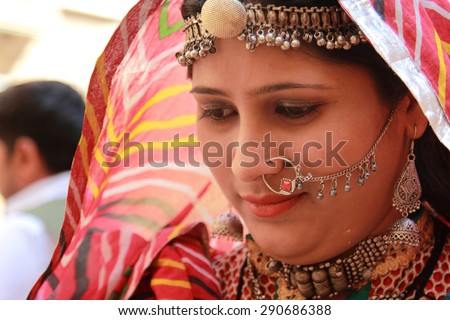 JAISALMER, INDIA - FEB 03: Unidentified Rajasthani woman dressed up in traditional costume and pose in front of a shop during Desert Festival on February 03, 2015 in Jaisalmer, Rajasthan, India.