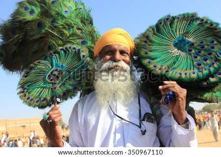 JAISALMER, INDIA - FEB 01: Unidentified traditional Rajasthani villager sells peacock feathers during the Desert festival held on February 01, 2015 in Jaisalmer, Rajasthan, India. - stock photo