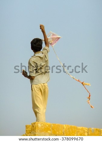 JAISALMER, INDIA - FEBRUARY 18: Unidentified boy flies kite from the roof of traditional house on February 18, 2011 in Thar Desert, India. Thar Desert forms natural boundary between India and Pakistan