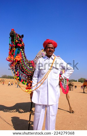 JAISALMER, INDIA - FEBRUARY 16: Unidentified man leads camel during Desert Festival on February 16, 2011 in Jaisalmer, India. Main purpose of Festival is to display colorful culture of Rajasthan - stock photo