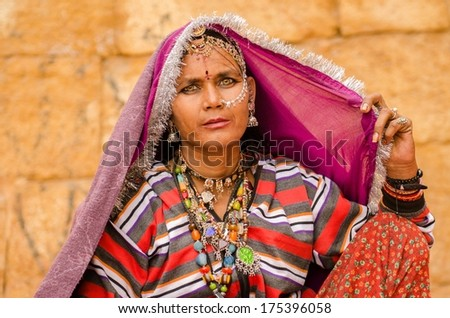 JAISALMER, INDIA - JAN 28: Rajasthani tribal women who dress in vibrant coloured dress and use lots of jewels are found near the Jaisalmer fort on 28 Jan 2014.