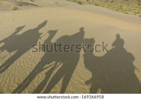 JAISALMER, INDIA - JAN 24: Shadows of camel herder and tourists in desert on January 24, 2013 in Jaisalmer, India. Camel riding activity is important income source for desert villagers. - stock photo