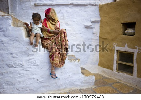 JAISALMER, INDIA - JAN 12: Unidentified Indian woman and her child live in Jaisalmer Fort in Thar desert on January 12, 2013 in Jaisalmer, India. Jaisalmer Fort is the only livable fort in India.  - stock photo