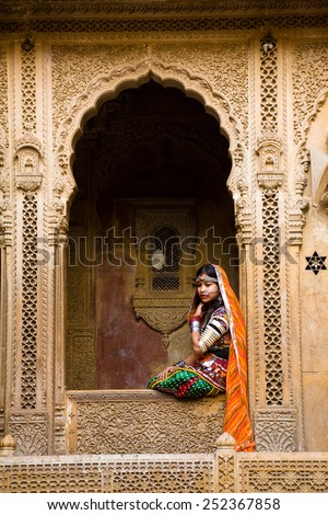 Jaisalmer, India - January 7, 2015 : An indian female tourist dressed up in traditional clothing and posing in the window of the Patwon Ki haveli in Jaisalmer, India - stock photo