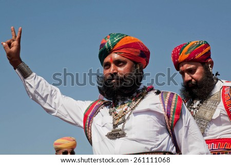 JAISALMER, INDIA - MAR 1: Beard man in indian dress show the victory sign during the contest of the Desert Festival on March 1, 2015. Every winter Jaisalmer takes the famous Desert Festival