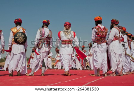 JAISALMER, INDIA - MAR 1: Beautiful men in old style dresses standing on stage during the contest Mr Desert during the annual festival on March 1 2015. Every winter Jaisalmer takes the Desert Festival