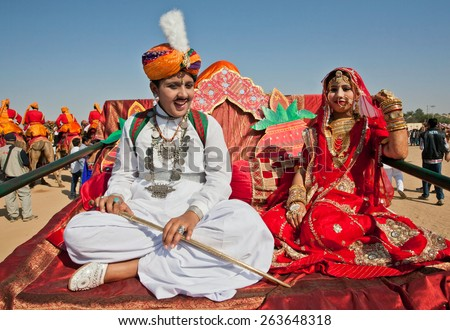 JAISALMER, INDIA - MAR 1: Beautiful young couple in national clothes sit on the camel cart during the famous Desert Festival on March 1, 2015. Every winter Jaisalmer takes famous Desert Festival - stock photo