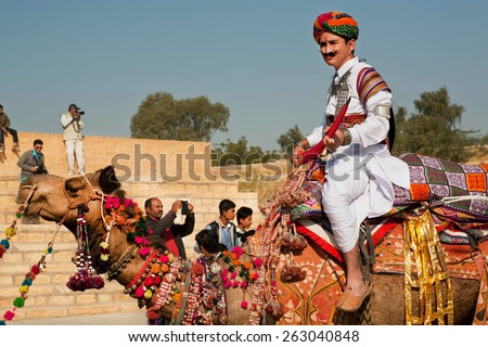 JAISALMER, INDIA - MAR 1: Camel rider in colorful dress goes past the tourist crowd of popular Desert Festival on March 1, 2015 in Rajasthan. Every winter Jaisalmer takes the Desert Festival - stock photo