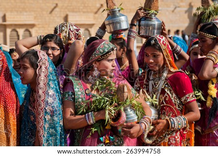 JAISALMER, INDIA - MAR 1: Cute indian girls chatting in the line of colorful women during the famous Desert Festival on March 1, 2015. Every winter Jaisalmer takes the Desert Festival of Rajasthan - stock photo