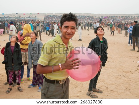 JAISALMER, INDIA - MAR 1: Happy young man with balloon walking in the crowd of people during the Desert Festival on March 1, 2015 in Rajasthan. Every winter Jaisalmer takes the famous Desert Festival - stock photo