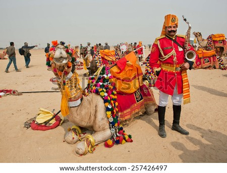 JAISALMER, INDIA - MAR 2: Musician in vivid form with saxophone dreaming near his camel before the start of Desert Festival on March 2, 2015. Every winter Jaisalmer takes the famous Desert Festival