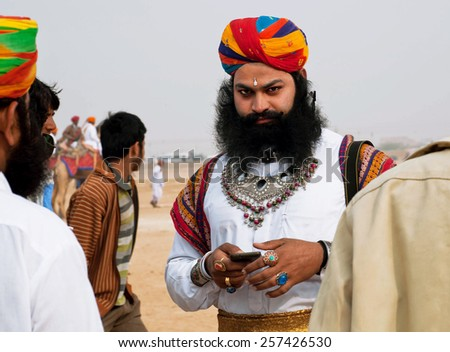 JAISALMER, INDIA - MAR 2: Serious Rajput with a beard and turban dials on a mobile phone during the famous Desert Festival on March 2, 2015. Every winter Jaisalmer takes the famous Desert Festival - stock photo