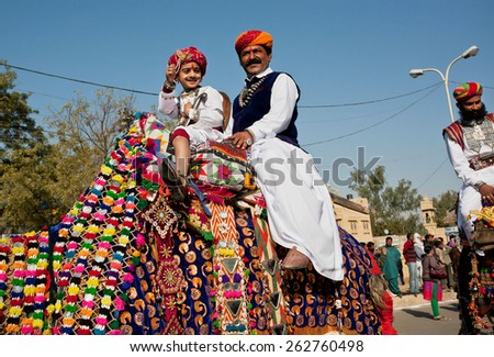 JAISALMER, INDIA - MAR 1: Unidentified boy and his father rides the camel in colorful caravan during the Desert Festival on March 1, 2015 in Rajasthan. Every winter Jaisalmer takes the Desert Festival - stock photo