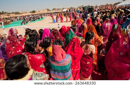 JAISALMER, INDIA - MAR 1: Wide view of the crowd of women waiting for the presentation and show on the Desert Festival on March 1, 2015 in Rajasthan. Every winter Jaisalmer takes the Desert Festival