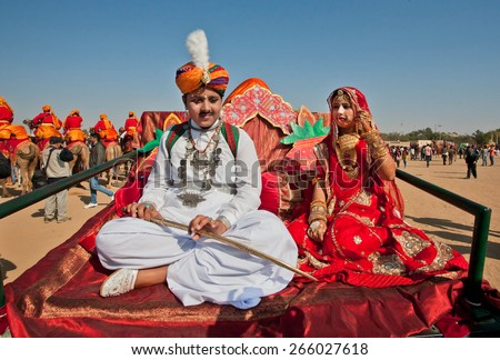 JAISALMER, INDIA - MAR 1: Young husband and beautiful indian wife waiting for the procession on the famous Desert Festival on March 1, 2015. Every winter Jaisalmer takes famous Desert Festival - stock photo