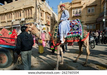 JAISALMER, INDIA - MAR 1: Young man in indian dress rides the camel on the street during the popular Desert Festival on March 1, 2015 in Rajasthan. Every winter Jaisalmer takes the Desert Festival - stock photo
