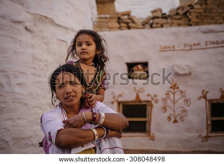JAISALMER, INDIA - MARCH 22 : Indian woman poses with her child in the street on March 22 , 2014 in Jaisalmer, India