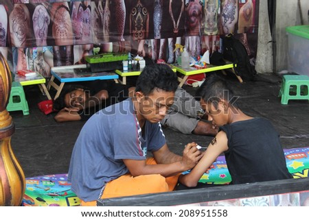 JAKARTA, INDONESIA, APR. 6: A tattooist works his art on the arm of a customer on April 6, 2014.  Tattoos are very popular amongst the male population with  trade  plied along the streets of the city. - stock photo