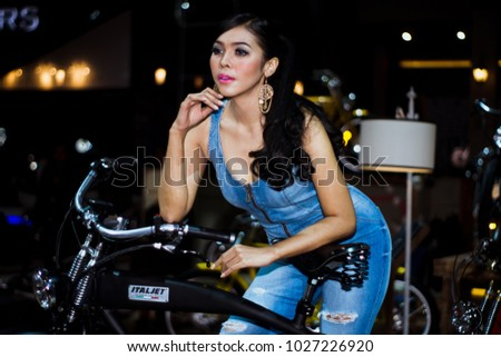 Jakarta, Indonesia, August 29, 2015 : An identified pretty asian young model is posing beside an Italian electric bike at Indonesia International Motor Show 2015.