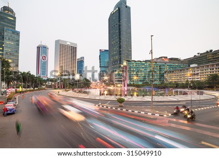 Jakarta, Indonesia - August 21 2015: Cars and buses rush through the Plaza Indonesia roundabout in Jakarta business district.