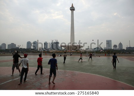 JAKARTA, INDONESIA - AUGUST 17, 2011: Children play football at the foot of the National Monument or the Monas in Jakarta, Central Java, Indonesia. - stock photo