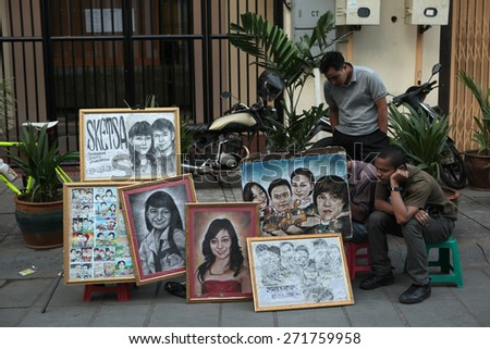 JAKARTA, INDONESIA - AUGUST 16, 2011: Street portrait painter offers his works in Old Batavia in Jakarta, Central Java, Indonesia. - stock photo