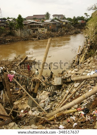JAKARTA, INDONESIA - February 12, 2007: Residents survey flood damage caused by severe El Niño floods along the Ciliwung, the capital's longest and most polluted river, in Jakarta, Java, Indonesia.