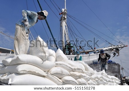 Jakarta, Indonesia - March 22, 2015 : Indonesian port workers unload a ship with a flour bags cargo in a traditional way in Sunda Kelapa, Jakarta, Indonesia.
