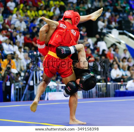 JAKARTA, INDONESIA: NOVEMBER 14, 2015: Gunawan from Indonesia (red) attempts to throw Lam Man Kan from Hong Kong (black) in the men's 52kg Sanda event at the 13th World Wushu Championship 2015. - stock photo