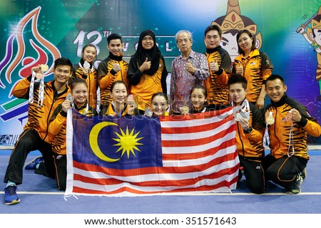 JAKARTA, INDONESIA - NOVEMBER 17, 2015: The Malaysian Wushu taolu athletes show off the medals they won at the 13th World Wushu Championship 2015 held at the Istora Senayan Stadium.