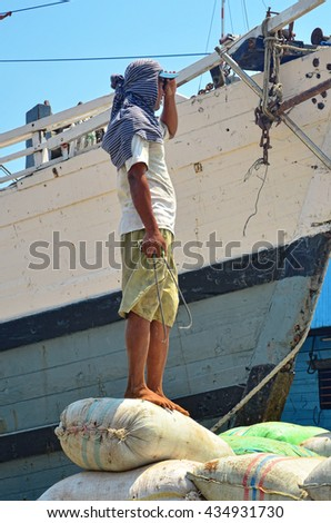 JAKARTA, INDONESIA - SEPTEMBER 12: Workers manually unload bags of cement from a ship at Sunda Kelapa Harbor on September 12, 2012 in Jakarta. There's currently 6.14 unemployment rate in Indonesia.