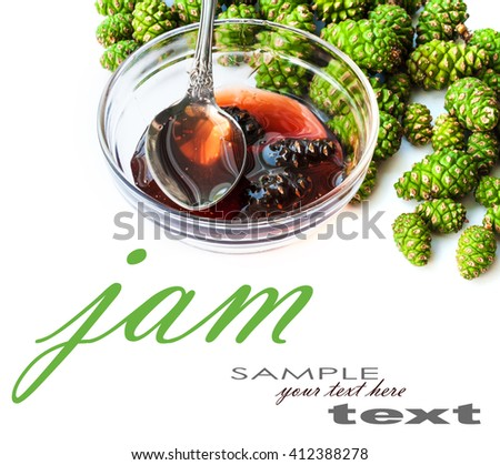Jam from cones in a plate and green cones on white table - stock photo