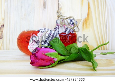Jam jar and rose flower,adapted as a wedding present on wooden background:Close up,select focus with shallow depth of field.