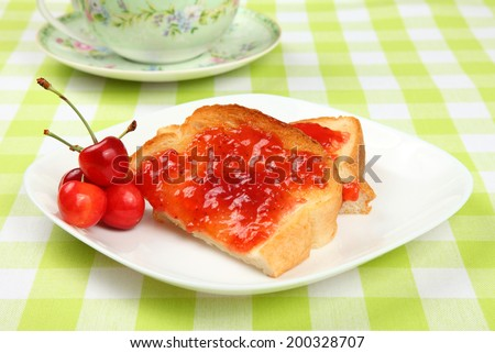 Jam toast with cherries/Jam toast/A photo of jam toast with fresh cherries on a checked cloth with teapot in background.