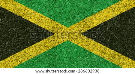 Jamaica flag texture on green grass - stock photo