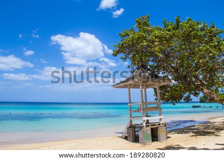 Jamaican Beach A. Caribbean white sand beach on the northern coast of Jamaica, near Dunn's River Falls and the town of Ocho Rios. - stock photo