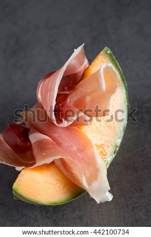 Jambon mix. Ham. Traditional Italian and Spanish salting, smoking, dry-cured dish - jamon Serrano and prosciutto crudo sliced with melon on grey background. Copy space. Closeup.