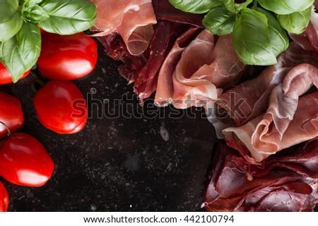 Jambon mix. Ham. Traditional Italian and Spanish salting, smoking, dry-cured dish - jamon Serrano and prosciutto crudo sliced with herbs and tomatos on dark stone background. Copy space. Closeup. - stock photo