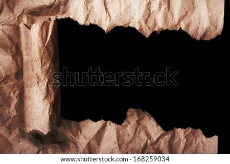 Jammed brown old torn paper with opening showing permanent black background with space place for text or picture - stock photo