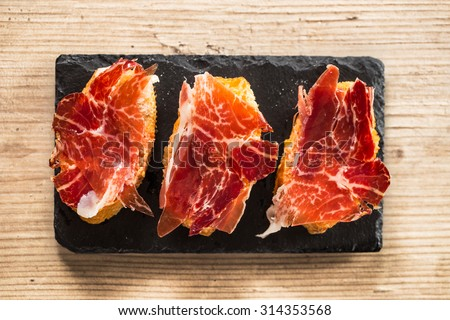 Jamon iberico, the best spanish ham tapas. Top view on a wooden table. - stock photo