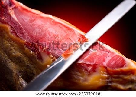Jamon. Jamon serrano. Traditional Spanish ham on black close up. Slicing Hamon iberico - stock photo