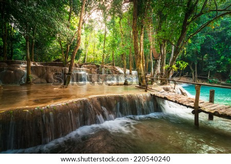 Jangle landscape of tropical rain forest landscape with wooden bridge and amazing turquoise water of Kuang Si cascade waterfall. Luang Prabang, Laos - stock photo