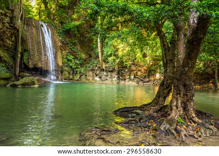 Jangle landscape with flowing turquoise water of third step Erawan cascade waterfall at deep tropical rain forest. Erawan Falls National Park at Kanchanaburi, Thailand - stock photo