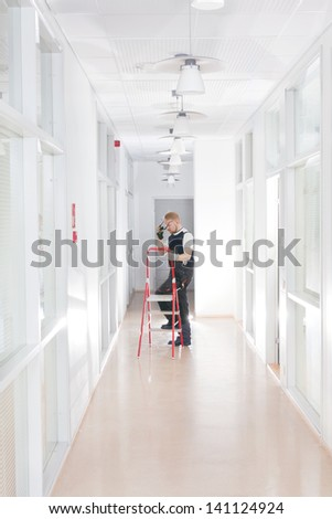 Janitor Climbing to Ladders at Office Corridor - stock photo
