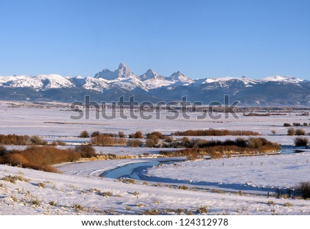 January and winter in the snow covered Teton Valley with the Teton river in the foreground and the Teton Peaks and Mountains in the background. - stock photo