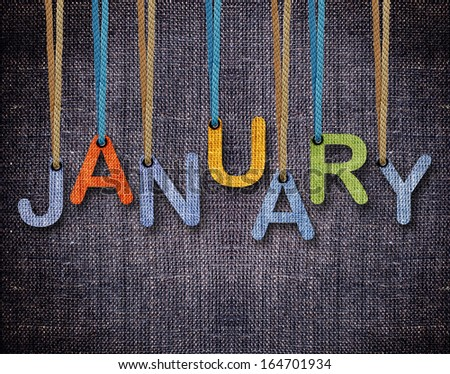 January letters hanging strings with blue sackcloth background. - stock photo