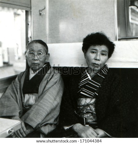 JAPAN - CIRCA 1950s: An antique photo shows Two women in kimono in a train