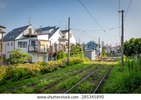Japan's train track in residental area on a sunny day - stock photo