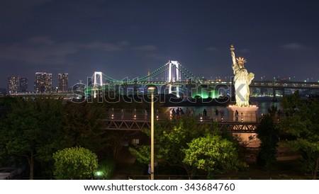 Japan skyline of Liberty statue and rainbow bridge from Odaiba - stock photo