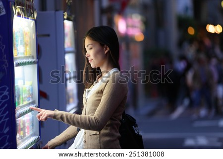 Japan vending machines - Tokyo woman buying drinks. Young student or female tourist choosing a snack or drink at vending machine at night in famous Harajuku district in Shibuya, Tokyo, Japan. - stock photo